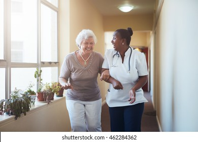 Portrait of happy healthcare worker and senior woman walking together. Senior patient having fun with her home caregiver.