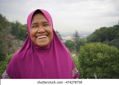 Portrait of happy and healthy aged woman at the park. Muslim woman. Strong,motivate and positive old woman. Malaysia woman face. Asian people.Indonesia muslim woman.