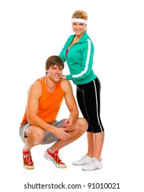 Portrait of happy healthy female and man in sportswear sitting on squat isolated on white
