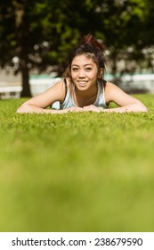 Portrait of happy healthy young woman lying on grass in park