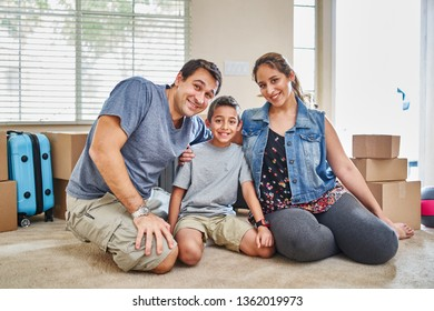 portrait of happy hispanic family sitting on carpet after moving into new home