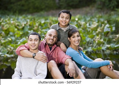 Portrait of happy Hispanic family with two boys outdoors