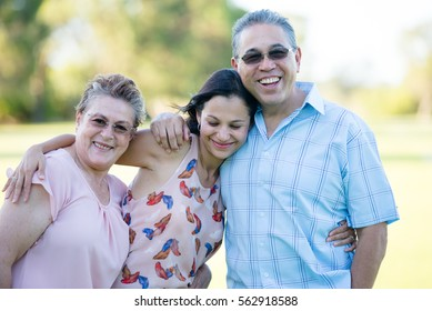 Portrait happy hispanic parents with attractive adult daughter leaning relaxed at dads shoulder outdoor, blurred background.