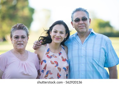 Portrait happy hispanic parents with attractive adult daughter, relaxed smiling outdoor park, blurred background.