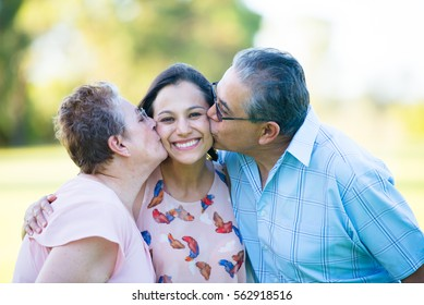 Portrait happy hispanic parents kissing attractive adult daughter with relaxed smiling outdoor park, blurred background.
