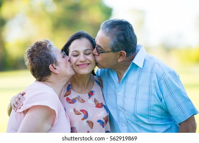 Portrait happy hispanic parents kissing attractive adult daughter with closed eyes, relaxed smiling outdoor park, blurred background.