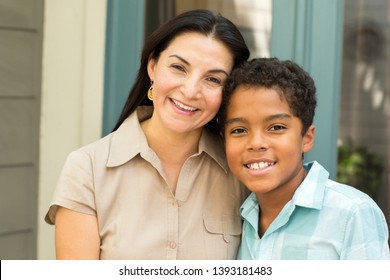 Portrait of a happy Hispnaic mother and son hugging