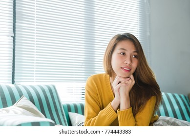 Portrait of happy home owner asian woman with perfect teeth smiling sitting on sofa in the living room in house interior. Relaxing asian woman sitting comfortable in sofa lounge chair smiling happy.