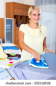 Portrait happy housewife ironing clothing at home interior