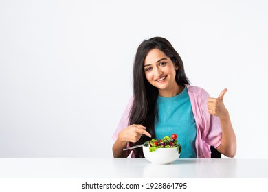 Portrait of a happy Indian asian pretty young woman eating fresh salad from a bowl while sitting isolated at table or desk against white background