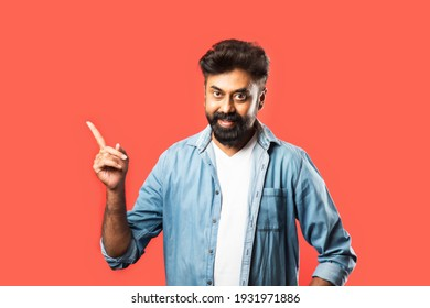 Portrait of a happy Indian bearded young man pointing fingers away at copy space isolated over red background