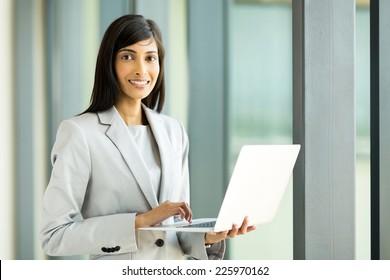 portrait of happy indian businesswoman using laptop computer