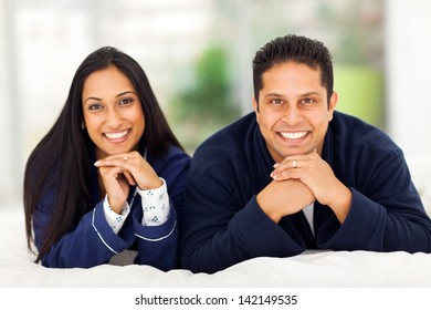 portrait of happy indian couple lying on bed