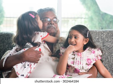 Portrait of happy Indian family at home. Grandchild kissing grandparent. Grandfather and granddaughters. Asian people living lifestyle.