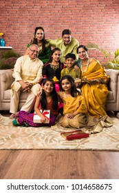 Portrait of happy Indian family in traditional wear sitting on sofa indoor