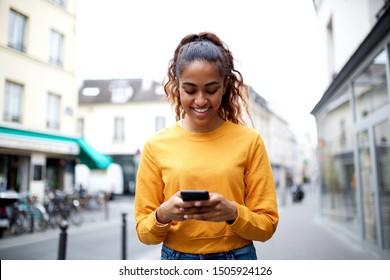 Portrait of happy Indian girl looking at mobile phone in city