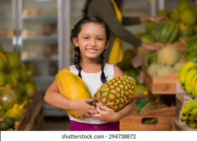 Portrait of happy Indian girl with pineapple and melon in her hands