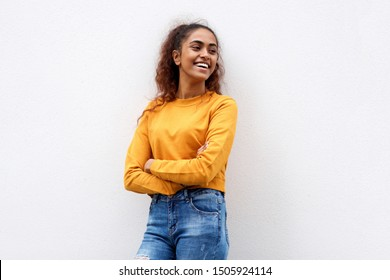 Portrait of happy indian girl smiling with arms crossed and looking away against white background