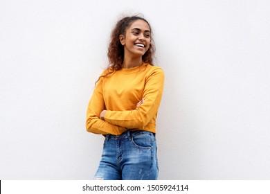 Retrato de una feliz hindú sonriendo con los brazos cruzados y mirando hacia otro lado contra un fondo blanco