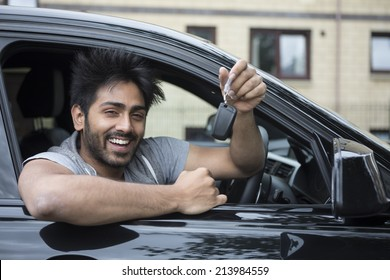 Portrait of a happy Indian man smiling in his new car and holding the key.