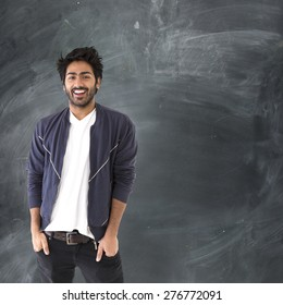 Portrait of a happy Indian man standing next to a blackboard.