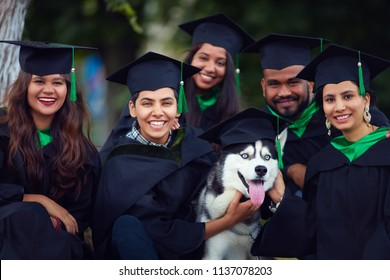 portrait of happy indian students friends in graduation gowns with pet dog