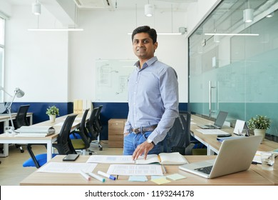 Portrait of happy Indian UX designer standing in modern office