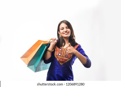 Portrait of a happy Indian woman or young girl carrying shopping bags, isolated over white background
