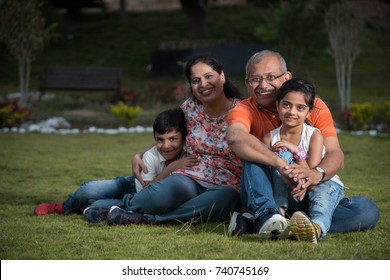 Portrait of Happy Indian/Asian Family while sitting on Lawn, outdoor