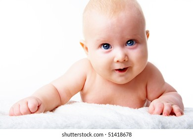 Portrait of happy infant crawling over fluffy rug on a white background