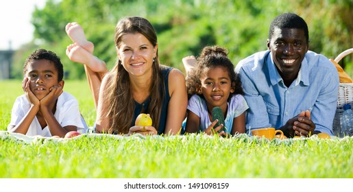 Portrait of happy interracial family with two children lying on blanket on green meadow, enjoying picnic