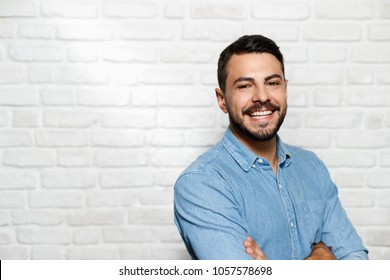 Portrait of happy Italian man smiling against white wall as background and looking at camera.