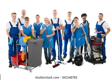 Portrait of happy janitors with cleaning equipment standing against white background