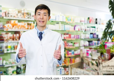 Portrait of happy japanese male specialist who is standing near selves in pharmacy.