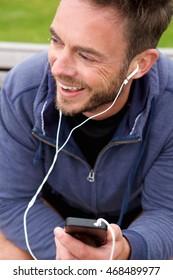 Portrait of happy jogger sitting with headphones
