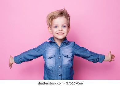 Portrait of happy joyful beautiful little boy. Studio portrait over pink background.