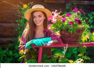 Portrait of happy joyful florist gardener woman in hat with flower pot of petunia and with shovel in home garden. Gardening and floriculture