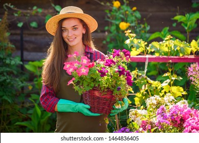 Portrait of happy joyful florist gardener woman in hat with flower pot of petunia outdoors. Gardening and floriculture. Growing flower in home garden