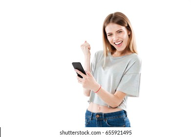 Portrait of a happy joyful girl holding mobile phone and celebrating a win isolated over white background