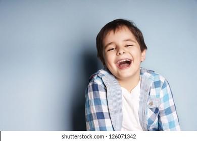 Portrait of happy joyful laughing beautiful little boy on blue background