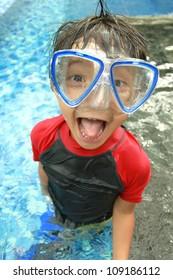 Portrait of happy joyful little boy swimming in the pool
