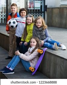 Portrait of happy junior school girls and boys in jackets
