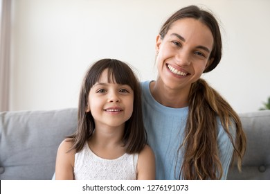 Portrait of happy kid girl and smiling mother looking at camera webcam making online call, cute child with mom vloggers recording video blog or vlog together, mommy and little daughter headshot