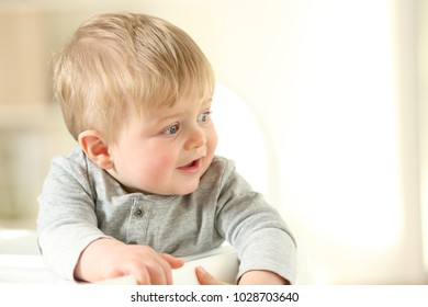 Portrait of a happy kid looking at side sitting on a high chair at home