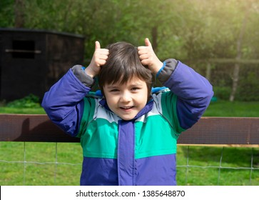 Portrait of happy kid standing next to animals cages making horns with fingers, Active child having fun in the farm and making horns by his hands , Cute little boy playing outdoors in spring or summer