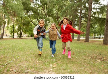 Portrait of happy kids running together in autumnal park