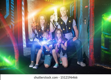 Portrait of happy kids and theirs parents with laser guns in colored beams during laser tag game in dark room