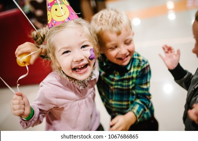 Portrait of happy kids wear festive caps, play with balloons, together celebrating birthday party. Girl and boys or brothers and sister. The concept birthday 2 - 3 years.