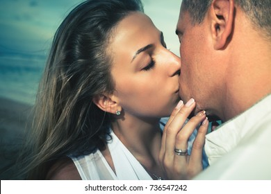 Portrait of happy kissing couple, closeup faces. Beach, sea view. Traveling at Bali. Honeymoon summer travel at Indonesia.