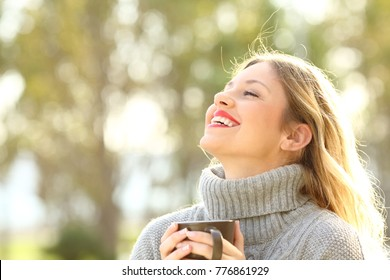 Portrait of a happy lady wearing a grey jersey breathing fresh air holding a cup of coffee in a park in winter